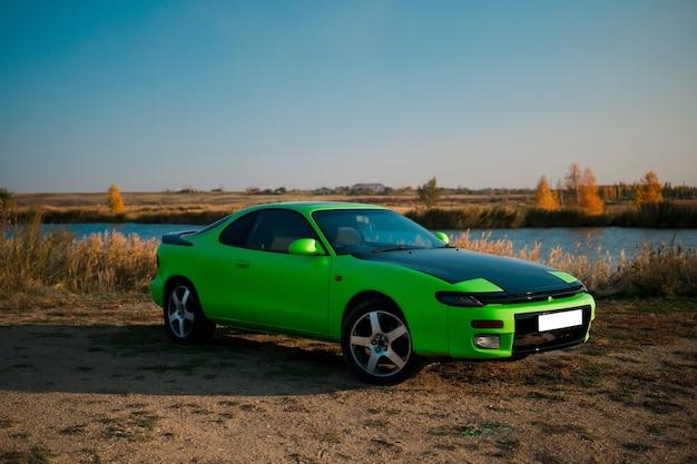 Зеленый и черный спортивный автомобиль-купе с большими колесами. японский олдтаймер.