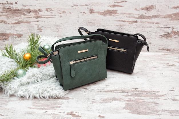 Зеленая и коричневая женская сумочка на деревянном фоне