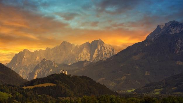 日没時の曇り空の下の緑と茶色の山々