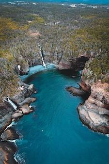 Зеленые и коричневые скалы у синего моря в дневное время
