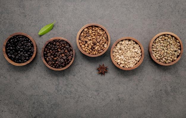 어두운 콘크리트에 숟가락으로 나무 그릇에 녹색과 갈색 unroasted 및 어두운 볶은 커피 콩.
