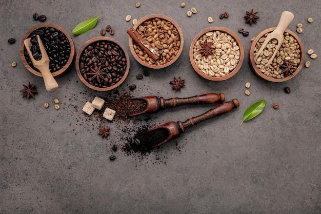 Зеленые и коричневые необжаренные и темные обжаренные кофейные зерна в деревянной миске с ложками на темном бетоне.