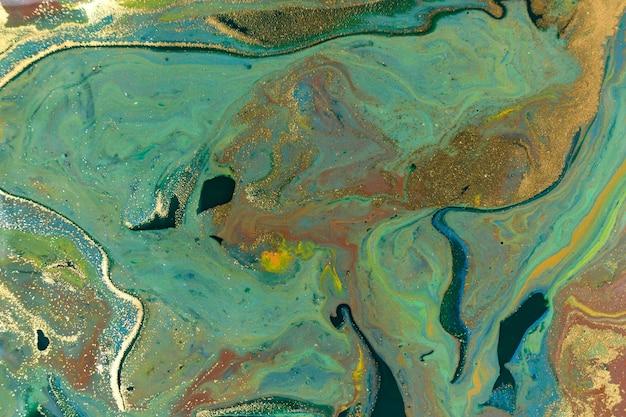 緑と金の霜降り液体の背景。流体アートの抽象的なテクスチャ。混合アクリルインク。