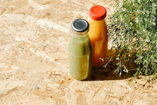 ブッシュの横にある緑とオレンジのデトックスジュース