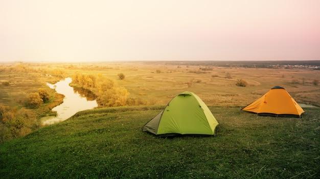 Зеленая и оранжевая палатка у реки