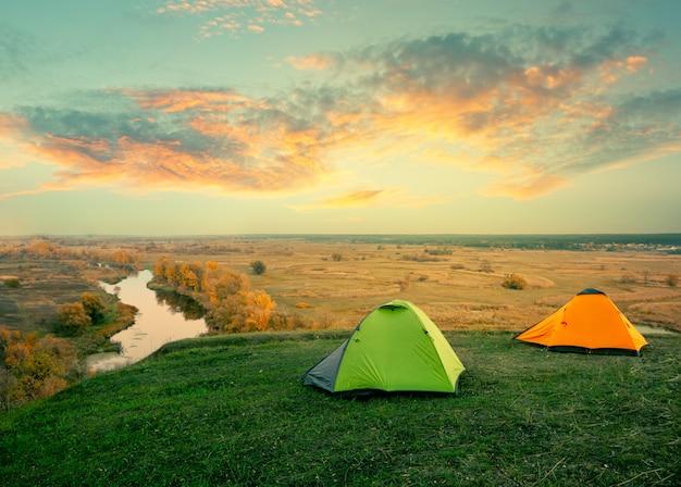 Зеленая и оранжевая палатка на берегу реки в солнечный летний день
