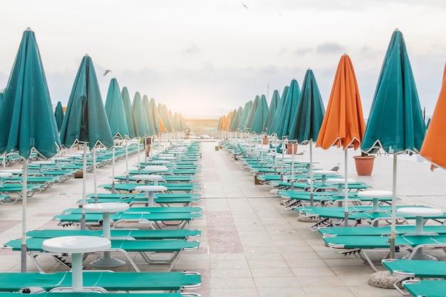 Зеленые и оранжевые зонтики и шезлонги у бассейна на летнем курорте