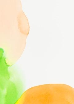 白い背景の上の緑とオレンジ色の水彩スポット