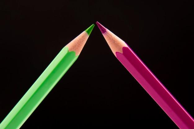 Зеленый и розовый карандаши для рисования на темном фоне. образование и творчество. досуг и искусство