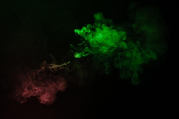 검정색 배경에 녹색과 분홍색 증기. 공간을 복사하십시오.