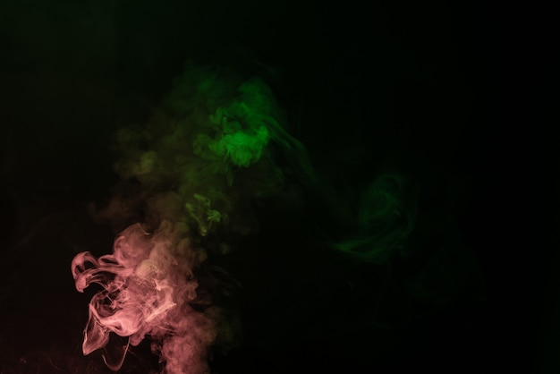 黒の背景に緑とピンクの蒸気。スペースをコピーします。