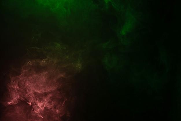 검은 색 표면에 녹색과 분홍색 증기. 공간을 복사하십시오.