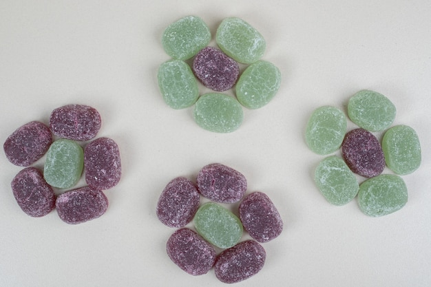 베이지 색 표면에 녹색과 보라색 젤리 사탕