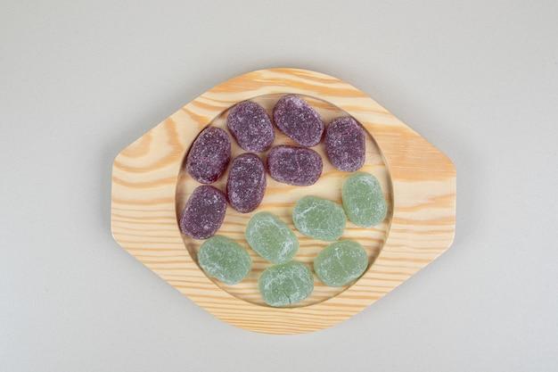 나무 접시에 녹색과 보라색 젤리 사탕