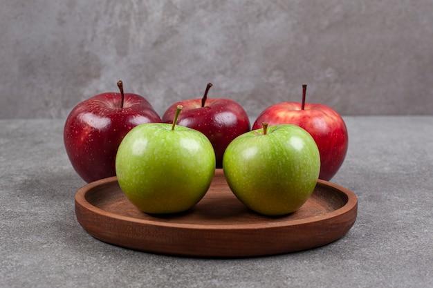 木製のキッチンボードに緑と赤のリンゴ
