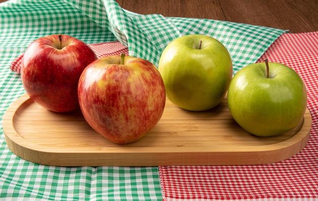 체크 무늬 테이블 보에 나무에 위치한 녹색 및 빨강 사과