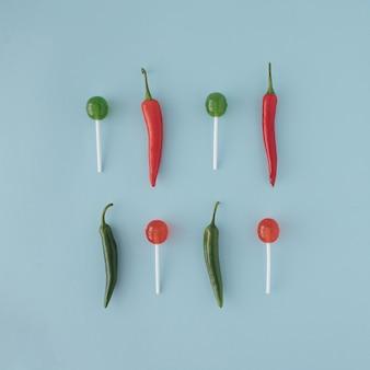Зеленые и красные перцы чили с красными и зелеными леденцами на палочке, расположенные в две строки на пастельно-синем фоне. минимальная творческая концепция питания.