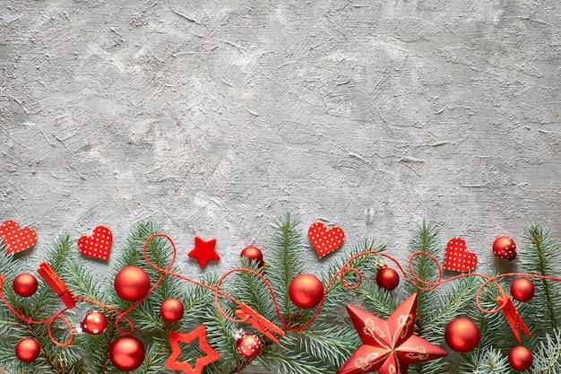 Зеленые и красные рождественские стены с еловыми ветками, сердца и рождественские безделушки на бетонном камне, пространство для текста