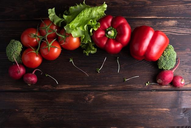 緑と赤の新鮮な野菜、赤唐辛子、大根、トマト、グリーンサラダは、暗い木製のテーブルの上に平らに置かれています。