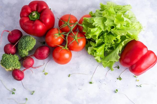 緑と赤の新鮮な野菜、赤ピーマン、大根、トマト、レタスは、平置きです。
