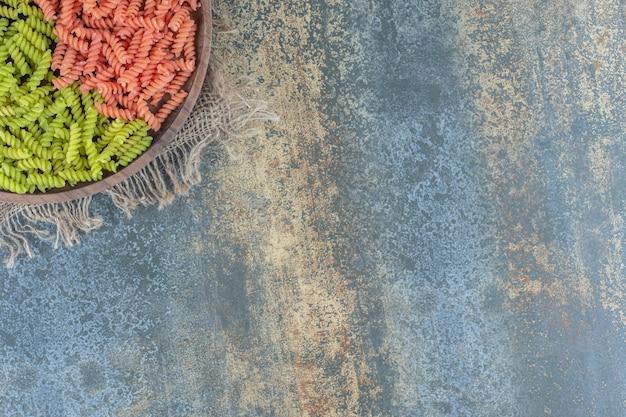 大理石の背景に、タオルの上のボウルに緑と赤のフジッリパスタ。