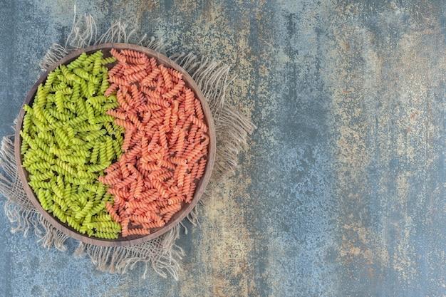 Зеленые и красные макароны фузилли в миске на полотенце на мраморной поверхности.