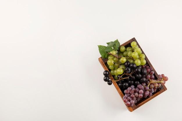 Грозди зеленого и красного винограда в деревянном ящике внизу