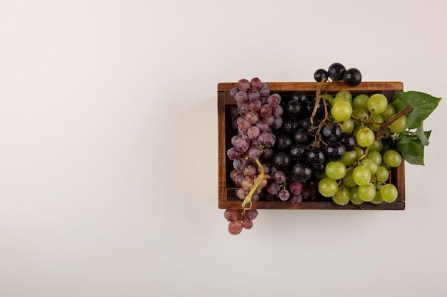中央の木製の箱に緑と赤のブドウの房
