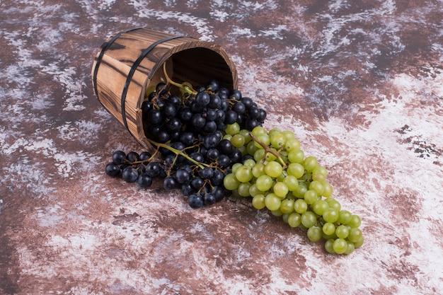 織り目加工のテーブルに木製のバケツに緑と赤のブドウの房