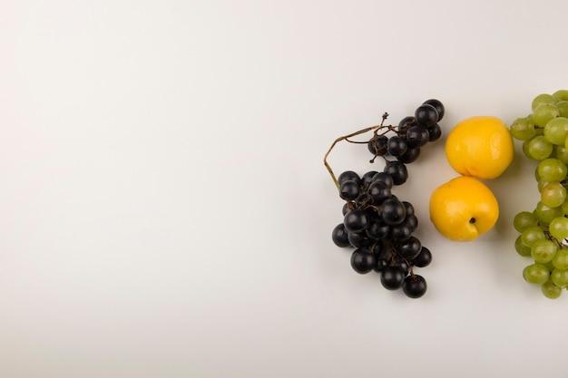 Грозди зеленого и красного винограда с желтыми персиками с правой стороны