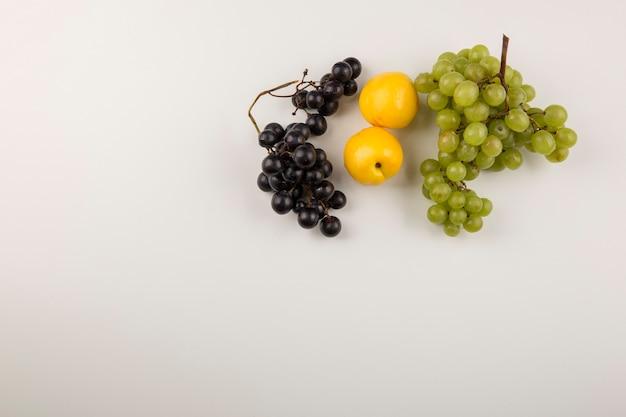Грозди зеленого и красного винограда с желтыми персиками