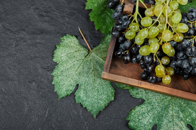木製のトレイに緑と赤のブドウ。