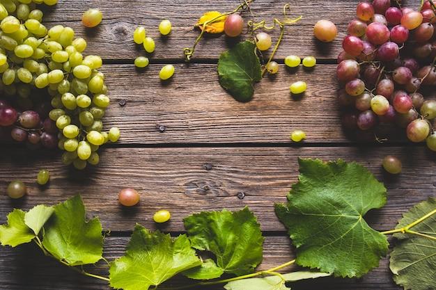 木製の背景に緑と赤のブドウ。健康食品