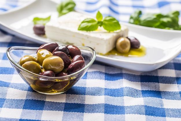백그라운드에서 올리브 오일과 그리스 죽은 태아의 치즈와 함께 그릇에 녹색 및 빨강 올리브.