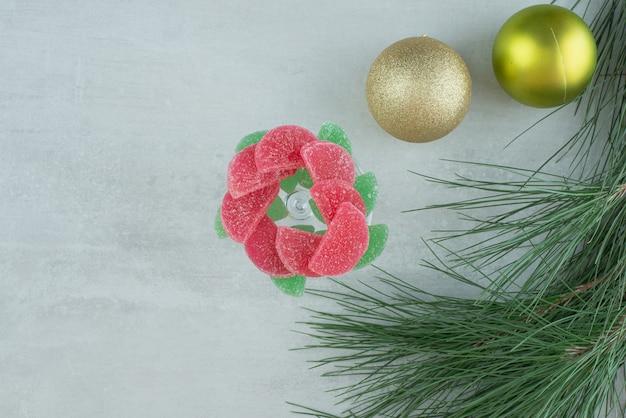 Зеленый и красный сахарный мармелад с елочными шарами на белом фоне. фото высокого качества