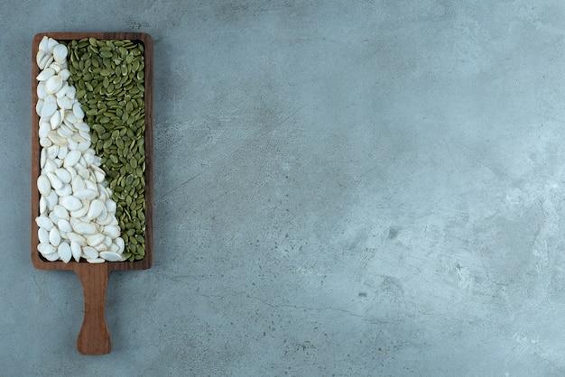 青の背景に緑と白のカボチャの種。高品質の写真