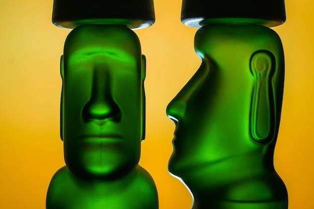 Скульптура гуманоида моаи зеленого и желтого цвета на оранжевом фоне
