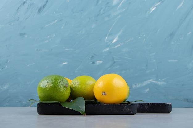Зеленые и желтые лимоны на черной разделочной доске