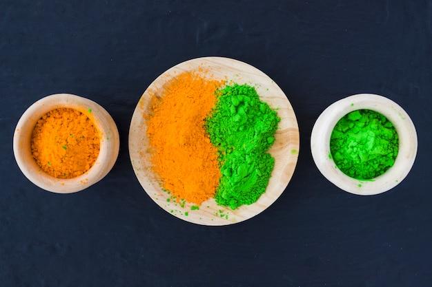 검은 배경에 나무 그릇과 접시에 녹색과 노란색 가루