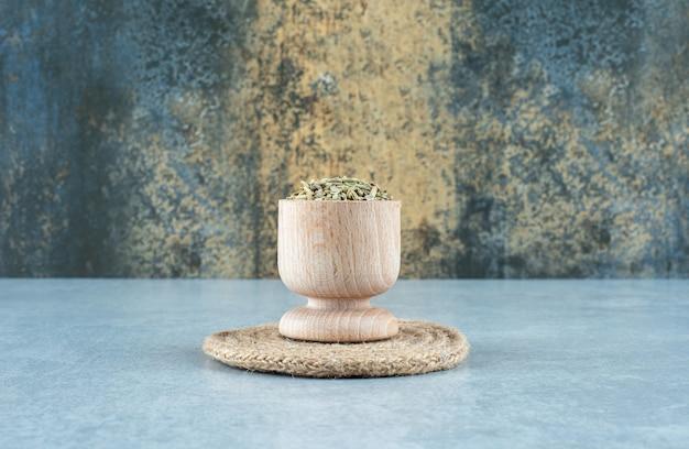 파란색 배경에 나무 컵에 녹색 아니스 씨앗. 고품질 사진