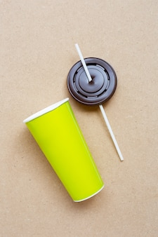 Green aper coffee cup with straw and plastic cap on plywood