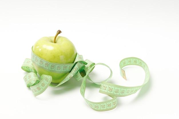 Зеленое яблоко и сантиметр на белом фоне. здоровое питание, похудение