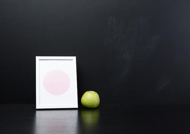 Зеленое яблоко и пустая белая деревянная фоторамка, черная стена