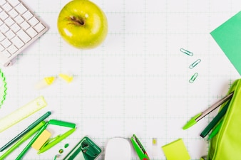 Green apple and kit of stationery