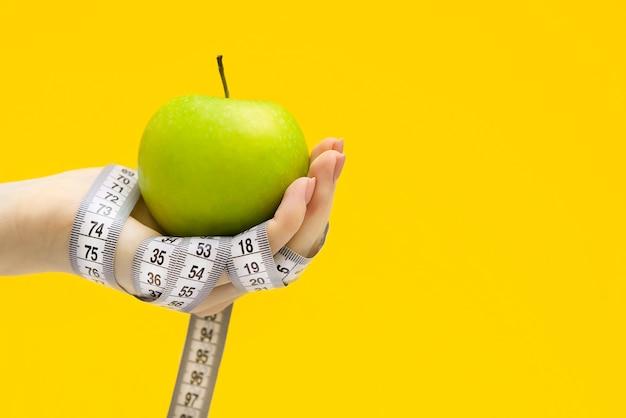 Зеленое яблоко и метр в женской руке
