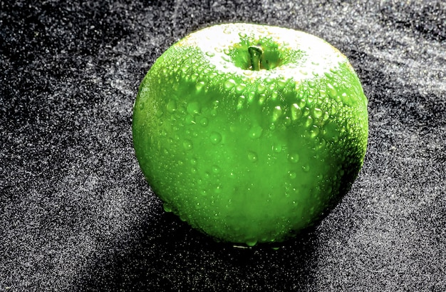 Green apple on the black texure