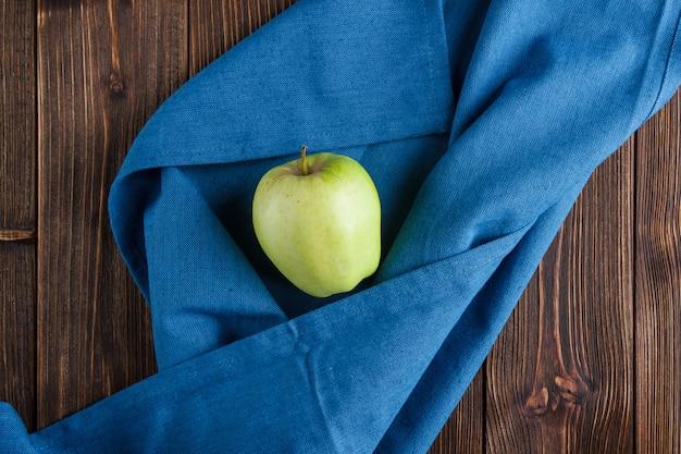 Mela verde su un panno blu e su un fondo di legno. vista dall'alto.