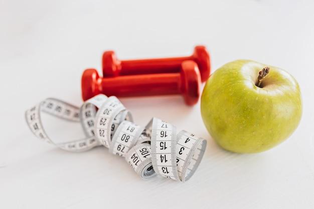 Зеленое яблоко, сантиметр и красные гантели. концепция здравоохранения, диеты и спорта