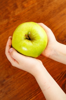 Green apple in the children's arm. top view