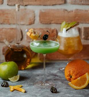 Green apple drink garnished with orange zest in long stem glass
